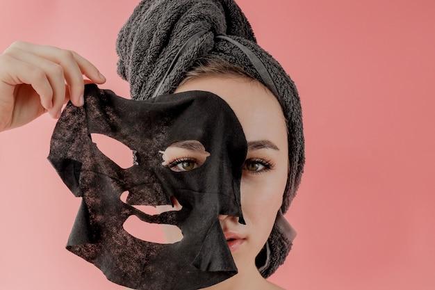 Junge frau wenden schwarze kosmetikgewebe-gesichtsmaske auf rosa hintergrund an. gesichtspeeling-maske mit holzkohle, spa-schönheitsbehandlung, hautpflege, kosmetologie. nahansicht