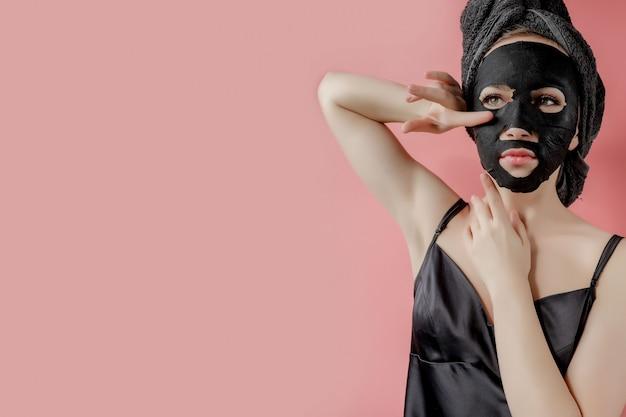 Junge frau wenden schwarze kosmetikgewebemaske auf rosa hintergrund an. gesichtspeeling-maske mit holzkohle, spa-schönheitsbehandlung, hautpflege, kosmetologie. nahansicht