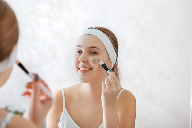 Junge frau wendet tongesichtsmaske an. junge frau verwendet hautpflege-schönheitsprodukte. teenager-mädchen verteilt tonmaske auf wange mit pinsel zu hause im badezimmer. self care beauty hautpflege spa-behandlung.