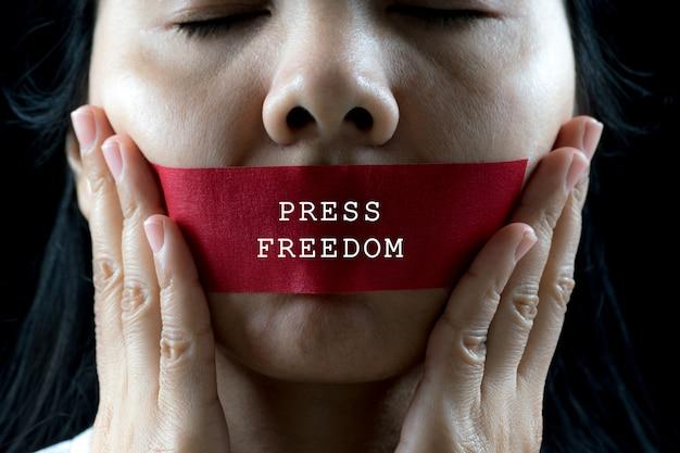Junge frau wickelte ihre montierung durch klebstreifen ein, hören sie auf, gewalttätigkeit, menschenrechts-tageskonzept zu missbrauchen.