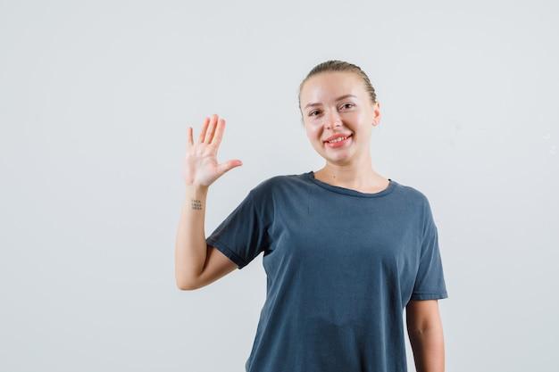 Junge frau winkt hand, um sich im grauen t-shirt zu verabschieden und froh zu schauen