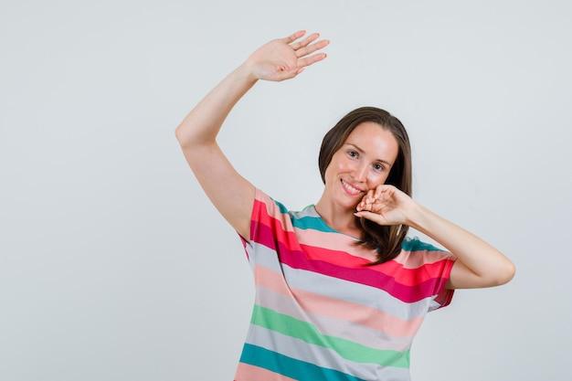 Junge frau winkt hand, um sich im t-shirt zu verabschieden und fröhlich auszusehen. vorderansicht.