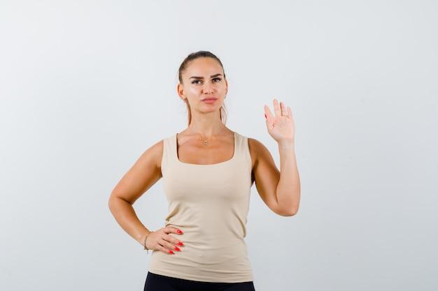 Junge frau winkt hand zum begrüßen, während hand auf hüfte im beige trägershirt hält und selbstbewusst aussieht
