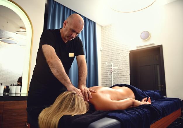 Junge frau wird von einem physiotherapeuten auf einem massagetisch in der klinik massiert. professionelle nackenmassage