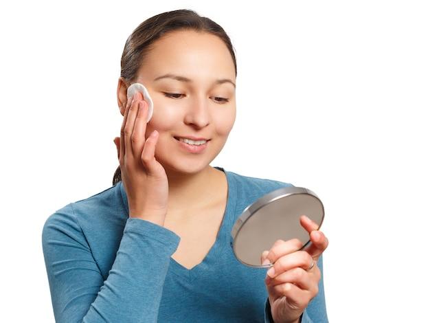 Junge frau wischt ihr gesicht mit einem wattepad mit lotion ab, schaut in den spiegel und lächelt.