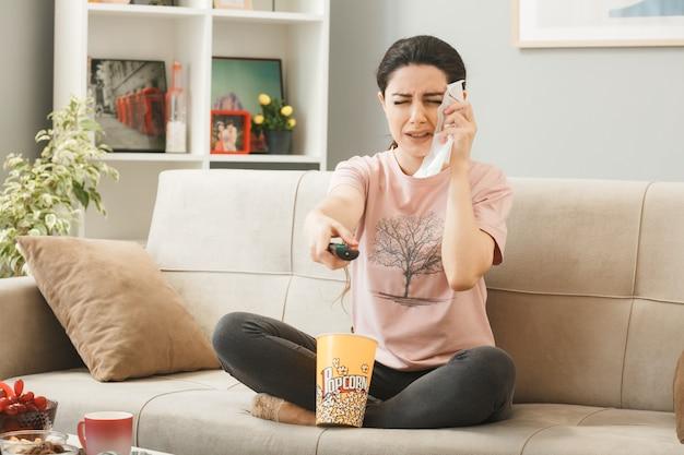 Junge frau wischt sich das gesicht mit einer serviette ab, die die tv-fernbedienung zur kamera hält, die auf dem sofa hinter dem couchtisch im wohnzimmer sitzt