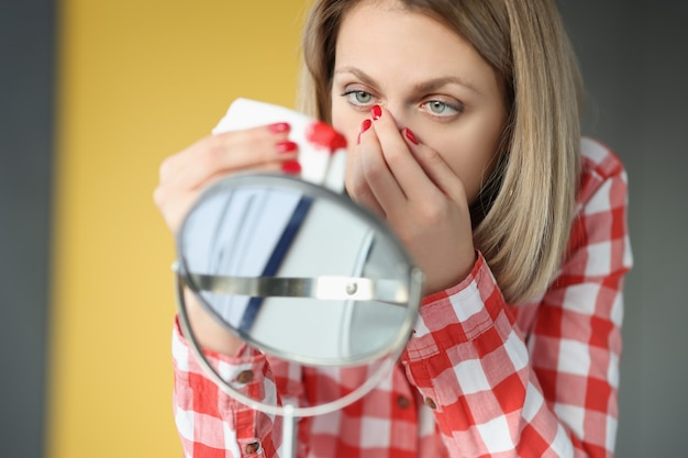 Junge frau wischt sich vor dem spiegel die nase mit einem taschentuch ab. wie man das nasenbluten-konzept stoppt