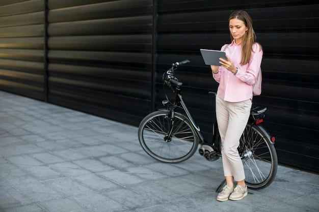 Junge frau witg digitale tablette und elektrisches fahrrad im freien