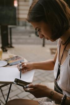 Junge frau zeichnet am sketchbook mit einem bleistift draußen auf der straße