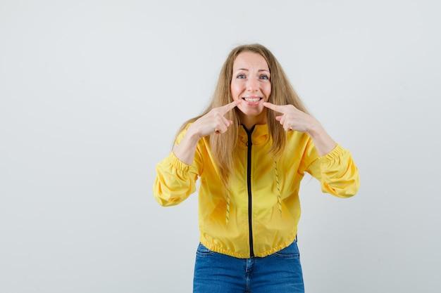 Junge frau zeigt auf den mund mit zeigefingern in gelber bomberjacke und blauer jeans und sieht optimistisch aus, vorderansicht.