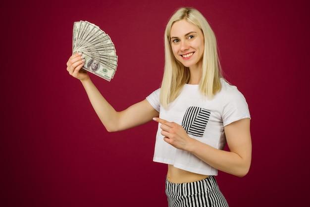 Junge frau zeigt auf einen stapel geld mit ihrem finger auf rubin