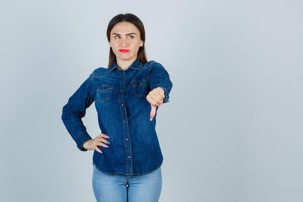 Junge frau zeigt daumen nach unten, während sie hand auf hüfte in jeanshemd und jeans hält und unzufrieden aussieht