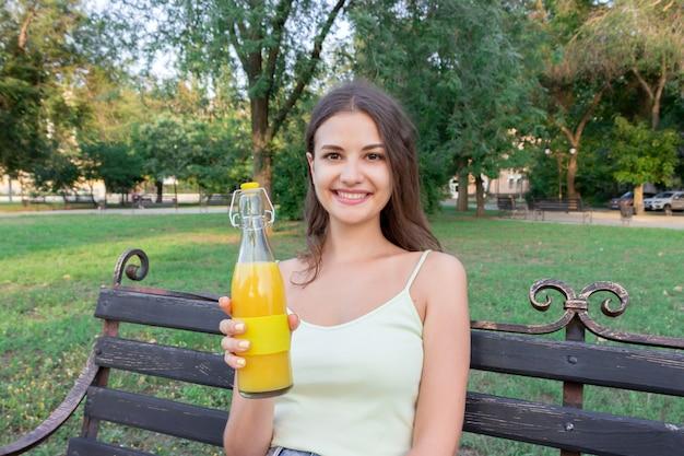 Junge frau zeigt eine flasche kühlen saft auf der bank im park