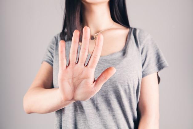 Junge frau zeigt halt mit der hand
