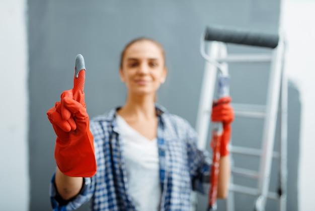 Junge frau zeigt handschuh in farbe, reparatur zu hause, glückliche frau, die wohnungsrenovierung macht, zimmerdekoration renoviert
