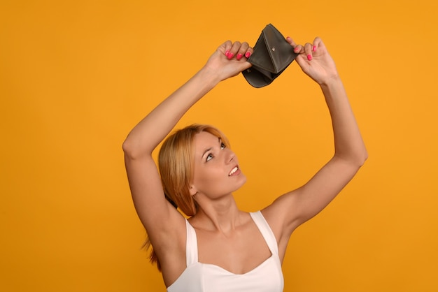 Junge frau zeigt ihre leere brieftasche. konkurs