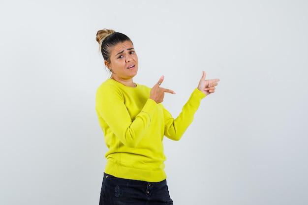 Junge frau zeigt mit zeigefingern in gelbem pullover und schwarzer hose nach rechts und sieht glücklich aus
