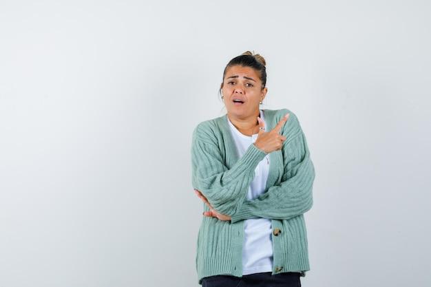 Junge frau zeigt nach rechts, hält die hand am ellbogen in weißem t-shirt und mintgrüner strickjacke und sieht ernst aus