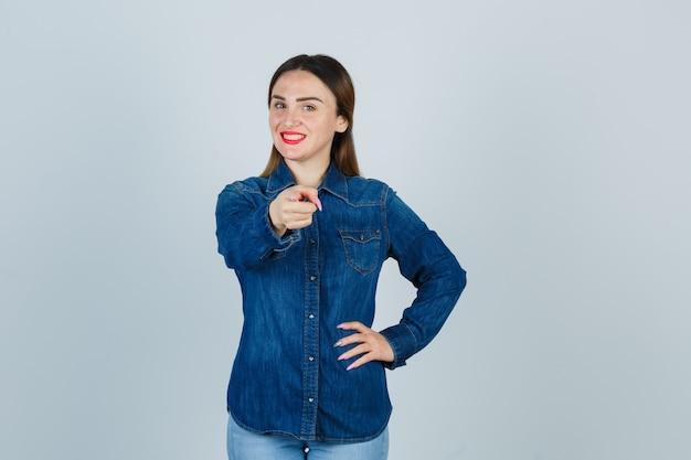 Junge frau zeigt nach vorne, während sie die hand auf der hüfte in jeanshemd und jeans hält und herrlich aussieht