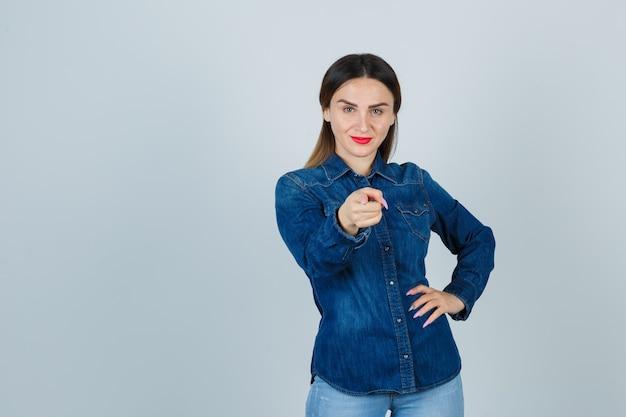 Junge frau zeigt nach vorne, während sie die hand auf der hüfte in jeanshemd und jeans hält und selbstbewusst aussieht