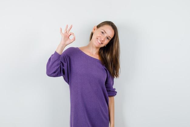 Junge frau zeigt ok zeichen im violetten hemd und schaut glücklich, vorderansicht.