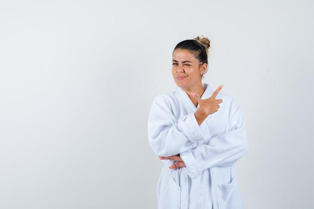 Junge frau zeigt zur seite, während sie im bademantel blinzelt und selbstbewusst aussieht
