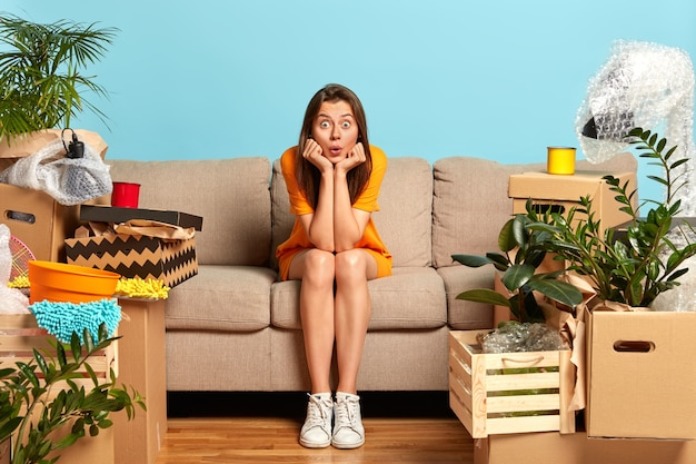 Junge frau zieht in neu gekaufte wohnung, posiert auf der couch mit geschocktem ausdruck
