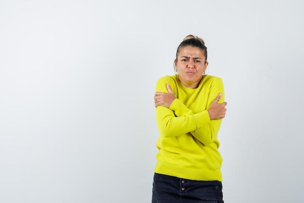 Junge frau zittert vor kälte, verzieht das gesicht in gelbem pullover und schwarzer hose und sieht gehetzt aus