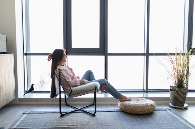 Junge frau zu hause, die auf modernem stuhl vor fenster sitzt, das in ihrem wohnzimmer entspannt
