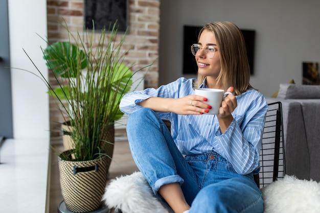Junge frau zu hause, die auf modernem stuhl vor fenster sitzt, der in ihrem wohnzimmer kaffee oder tee trinkt
