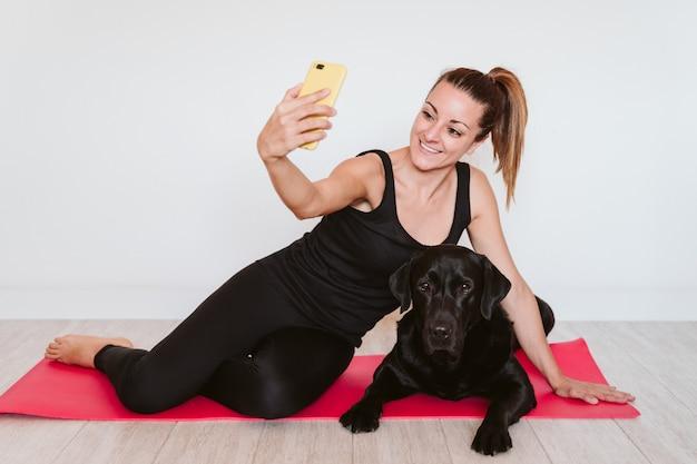 Junge frau zu hause entspannt mit mobilheim. außerdem sitzt sie mit ihrem schwarzen labrador-hund auf einer yogamatte. technologie und