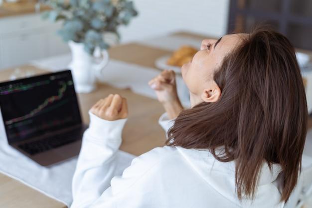Junge frau zu hause in der küche in einem weißen hoodie mit einem laptop, ein wachstumsdiagramm auf dem bildschirm