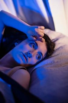 Junge frau zu hause mit geheimnisvollen schlafzimmerlichtern