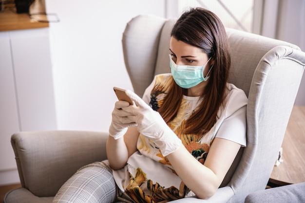 Junge frau zu hause mit maske und handschuhen, die smartphone betrachten und tippen. bleib zuhause. weltpandemie.
