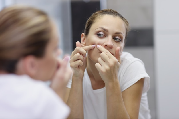 Junge frau zu hause schaut in den spiegel und drückt einen pickel aus. problemhautpflege, handreinigung