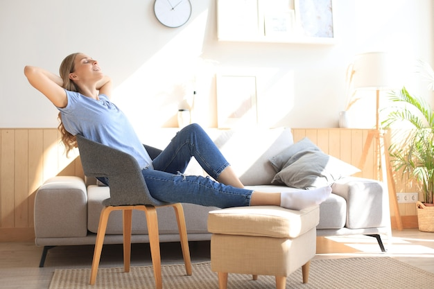 Junge frau zu hause sitzt auf einem modernen stuhl vor dem fenster und entspannt sich in ihrem wohnzimmer.