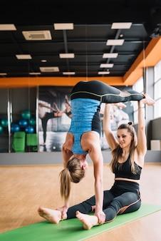 Junge frau zwei, die acro yoga in der turnhalle tut
