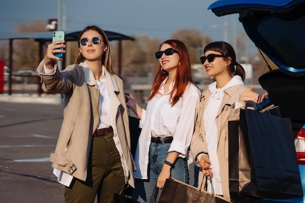 Junge frauen am auto mit einkaufstüten. mädchen machen selfie
