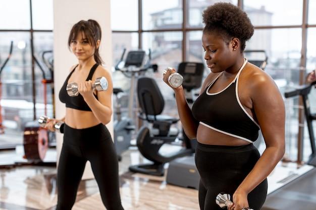 Junge frauen an der turnhalle trainierend mit gewichten