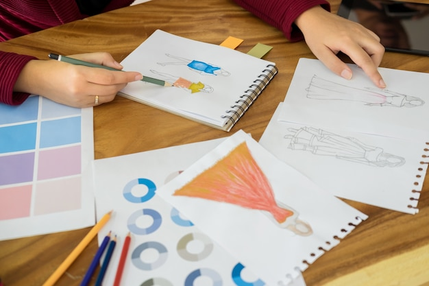 Junge frauen arbeiten als modedesigner zeichnung skizzen für kleidung in atelier papier am arbeitsplatz studio.