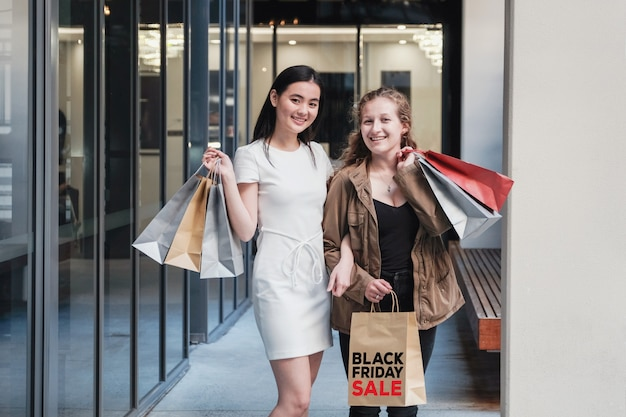 Junge frauen asiatischer und kaukasischer abstammung, die einkaufstaschen tragen,