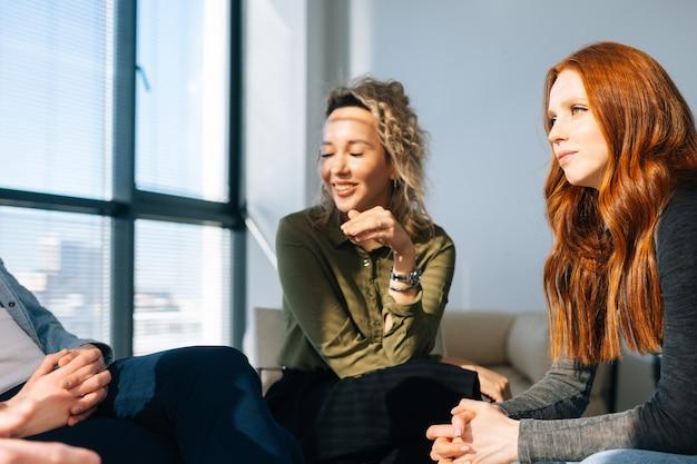 Junge frauen aus der nähe, die während des brainstormings von startprojekten in einem modernen büroraum in der nähe des fensters an einem sonnigen tag aufmerksam den kollegen zuhören.