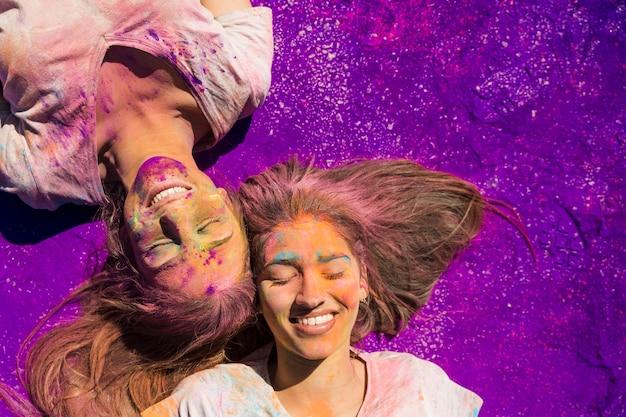 Junge frauen bedeckt mit dem holi pulver, das auf purpurroter farbe liegt