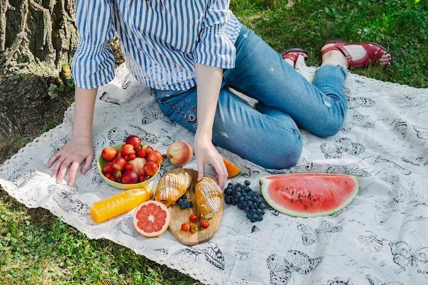 Junge frauen bei einem picknick, die nach einem croissant greifen.