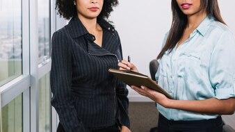 Junge Frauen des Afroamerikaners mit Dokumenten nähern sich Fenster