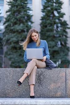 Junge frauen, die am laptop im stadtplatz arbeiten