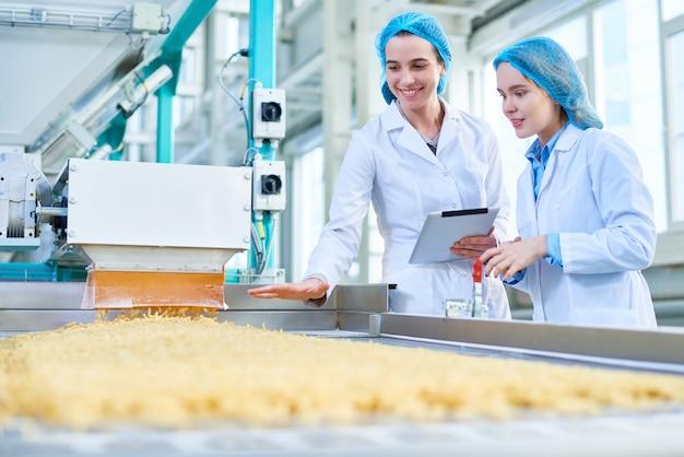 Junge frauen, die an der lebensmittelfabrik arbeiten