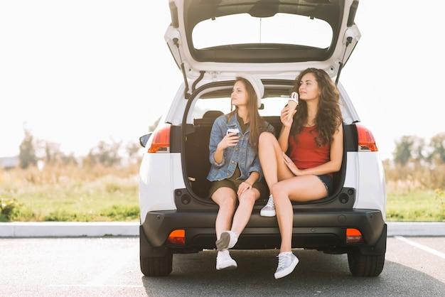 Junge frauen, die auf autokofferraum sitzen