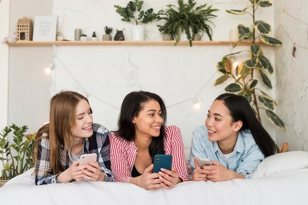 Junge frauen, die auf bett mit smartphones liegen