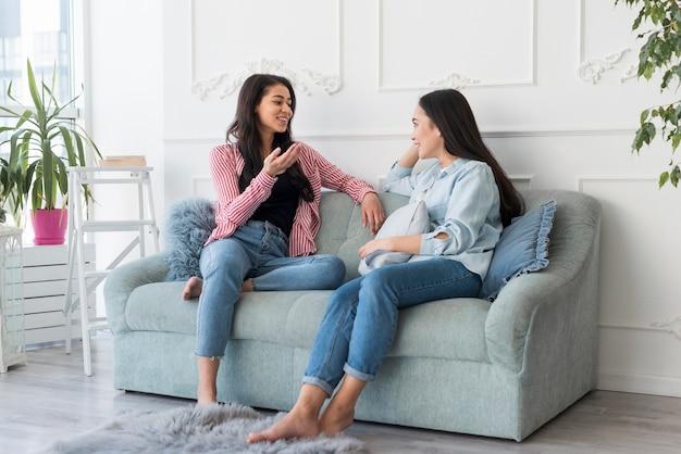 Junge frauen, die auf couch sitzen sprechen